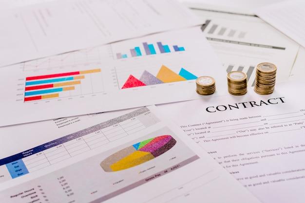 Monete impilate sui documenti del contratto di acquisto che vendono beni e analisi dei profitti.