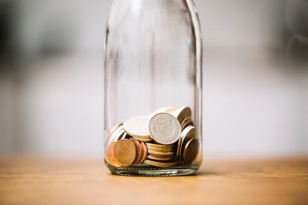 Monete nella bottiglia di vetro sulla superficie in legno