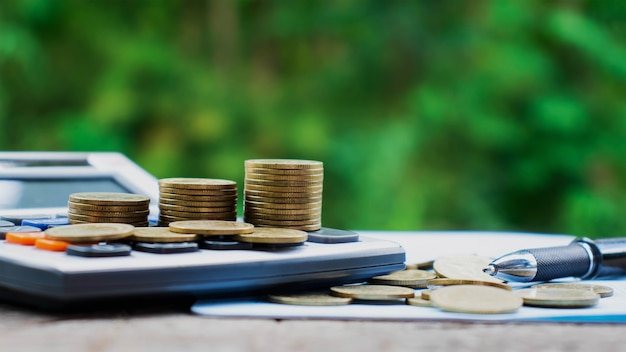 Monete o soldi su calcolatrici, concetti di contabilità finanziaria e risparmi
