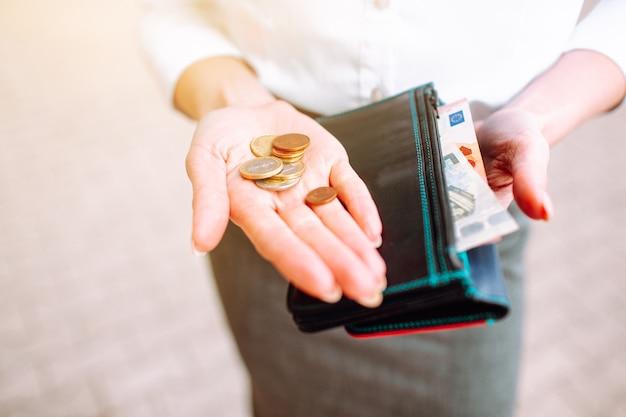 Monete sulla mano di una donna che indossa tuta da ufficio