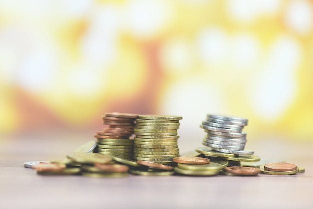 Monete sulla tavola - mucchio della moneta dorata, moneta d'argento e moneta di rame sul concetto finanziario dei soldi di legno