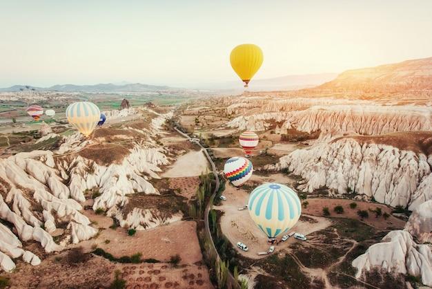 Mongolfiere colorate che sorvolano la valle rossa in cappadocia,