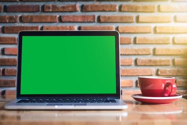 Monitor verde dello schermo del computer portatile del modello sulla tavola di legno