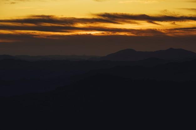 Montagna panoramica e fondo drammatico di tramonto del cielo in dorato