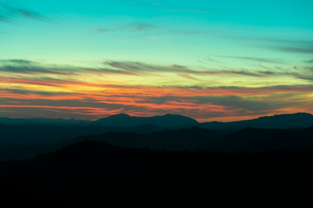 Montagna panoramica e fondo drammatico di tramonto del cielo