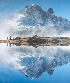 Montagna riflessa nell'acqua nelle alpi con alcune persone che fanno un'escursione