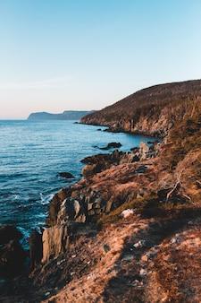 Montagna rocciosa di brown accanto al mare blu sotto cielo blu durante il giorno