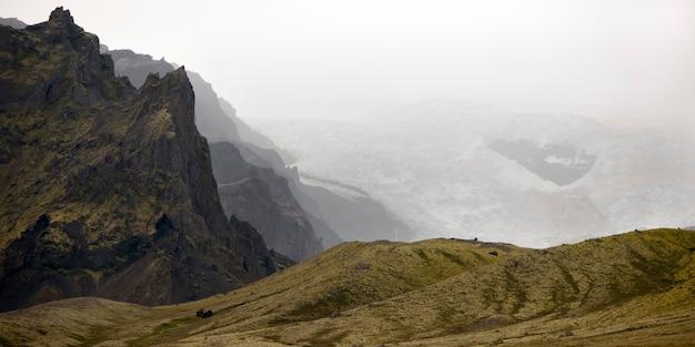 Montagna scoscesa, ghiacciaio nebbioso, dolci colline