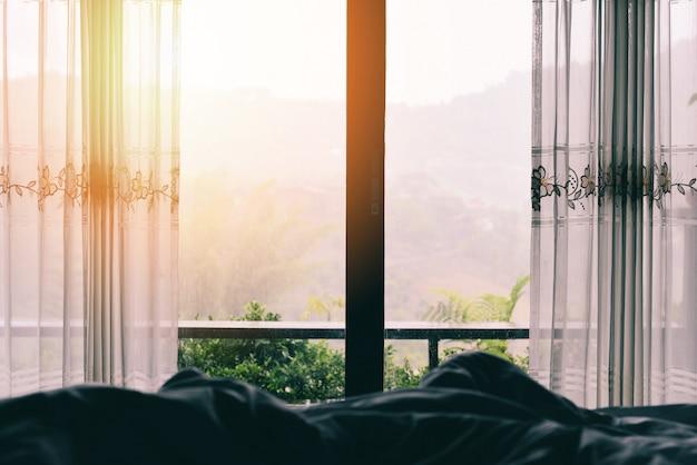 Montagna verde della natura di vista della finestra nel letto alla mattina della camera da letto e alla luce solare - vetro di finestra con drappi