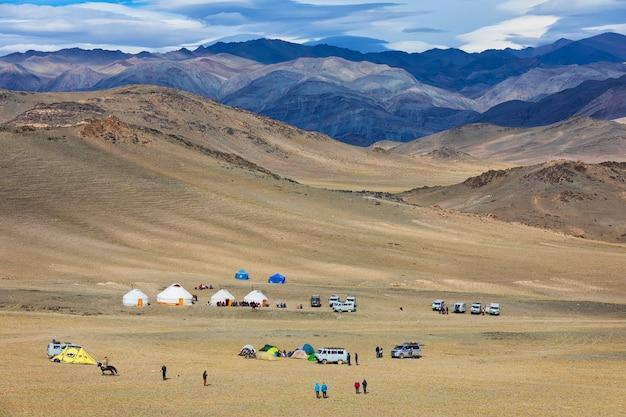 Montagne e valle di altai con piccole yurte mongole e automobili davanti alle montagne in mongolia occidentale