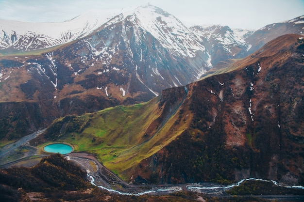 Montagne innevate e lago blu nella valle verde