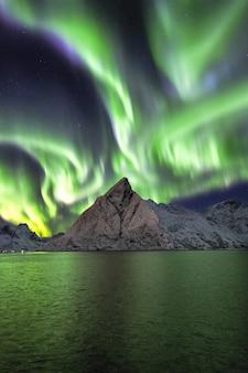 Montagne innevate sotto la bellissima aurora boreale nel cielo