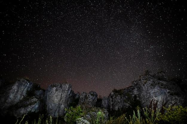 Montagne rocciose e cielo notturno stellato