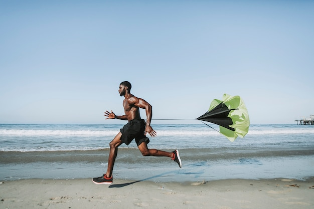 Montare l'uomo con un paracadute in esecuzione in spiaggia