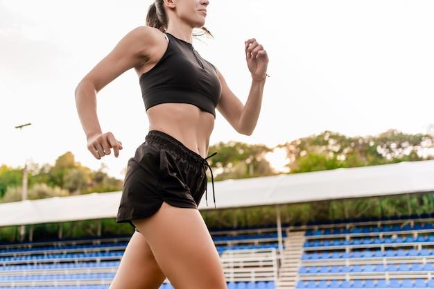 Montare la bella donna in esecuzione e fare jogging sullo stadio al mattino