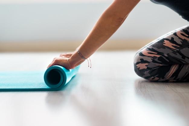 Montare la bella donna rotolando fitness, pilates o tappetino yoga prima o dopo aver allenato davanti alla finestra nel club studio di yoga oa casa. vista alta vicina delle gambe e del corpo. hobby sano, benessere