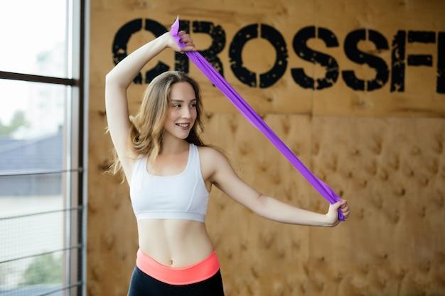 Montare la donna di bellezza che si esercita in studio fitness con elastico in palestra