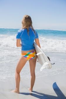 Montare la ragazza surfista sulla spiaggia con la sua tavola da surf