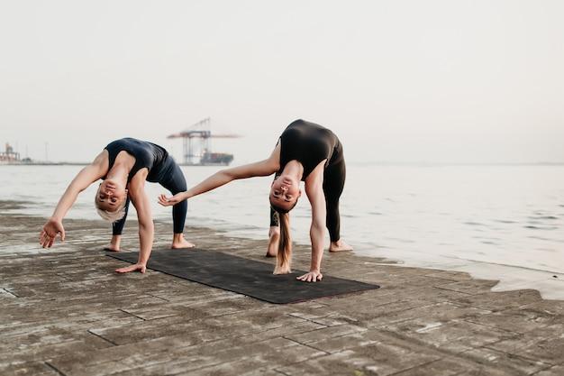 Montare le donne sulla spiaggia facendo acro yoga sport si esercita insieme vicino al mare