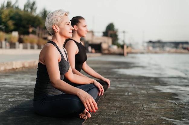 Montare le donne sulla spiaggia meditando insieme all'aperto