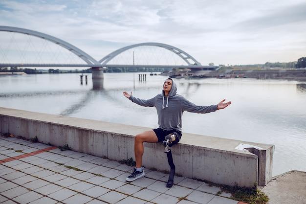Montare uno sportivo handicappato caucasico sano con gamba artificiale e felpa con cappuccio sulla testa che si siede sulla banchina con le braccia aperte.