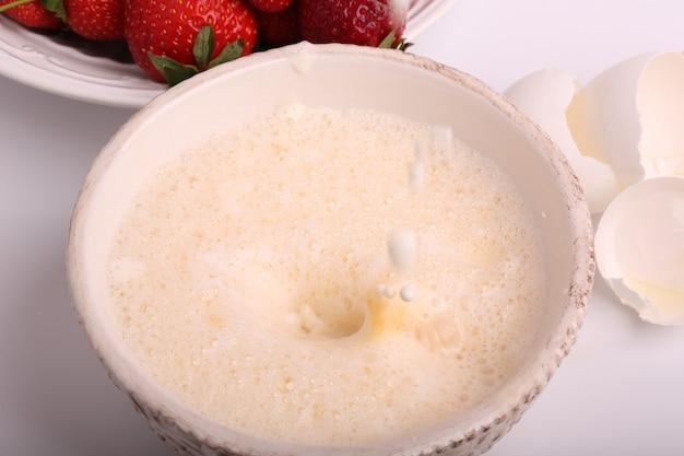 Montato a una schiuma le uova in una ciotola su un fuoco molle selettivo bianco del fondo