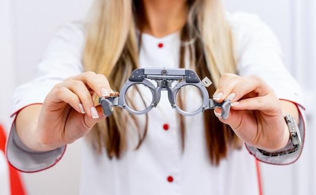 Montatura di prova oftalmologica e occhiali di prova nelle mani della donna