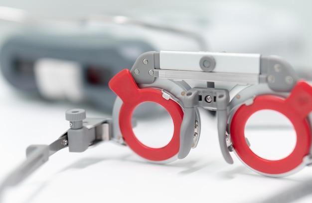 Montatura per occhiali con lente di prova ottica con pd meter sullo sfondo