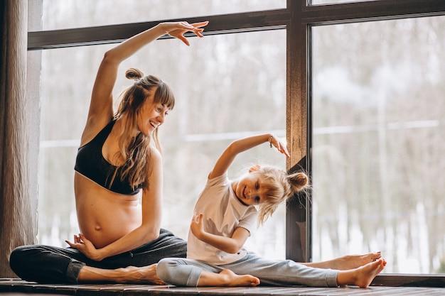 Mopther incinta che fa yoga con la piccola figlia