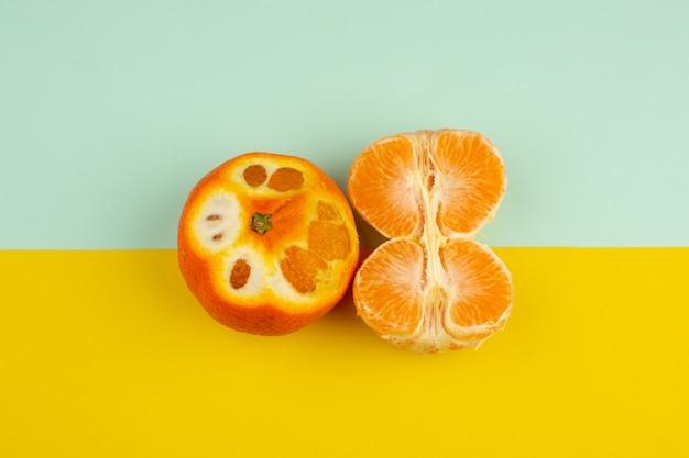 Morbido acido arancio del mandarino della frutta fresca sul pavimento blu-giallo
