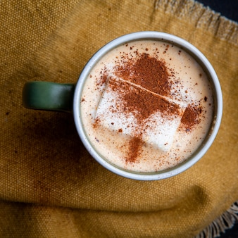 Morbido caffè al latte in una tazza piatta giaceva sul pezzo di sacco
