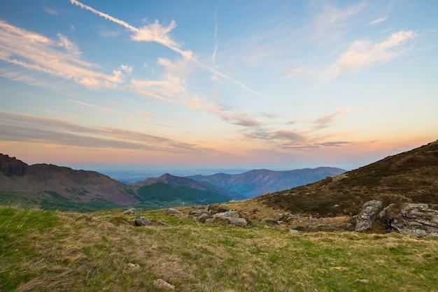 Morbido cielo color pastello sopra le vette rocciose, le creste e le valli delle alpi al crepuscolo.