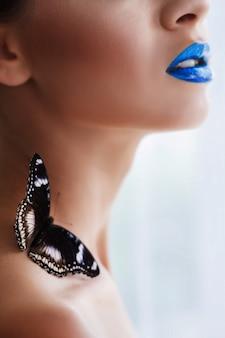 Morbido ritratto su uno sfondo bianco di una ragazza con una vibrante farfalla sulla spalla. labbra blu