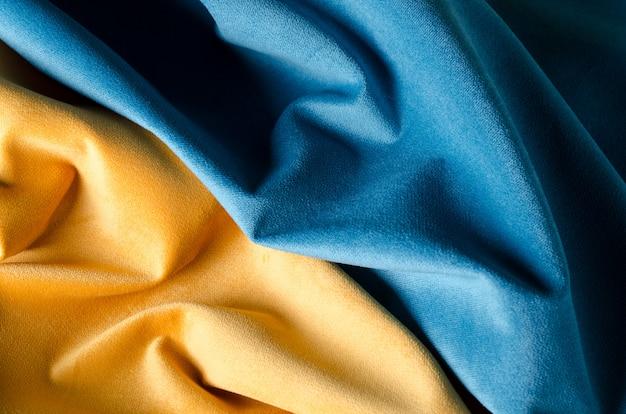 Morbido tessuto di velluto giallo e blu. colori della bandiera ucraina. tessuto trama di sfondo.