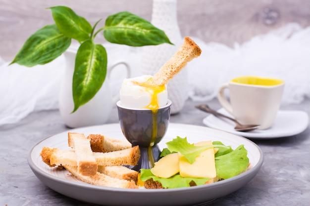 Morbido uovo di pollo bollito, crackers, pezzi di formaggio e lattuga su un piatto sul tavolo