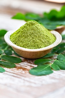Moringa in polvere in ciotola di cocco con originali foglie di moringa fresche
