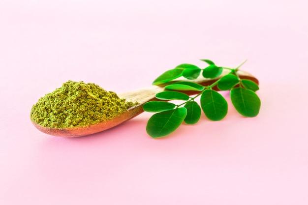 Moringa in polvere in cucchiai di legno con foglie originali di moringa fresche