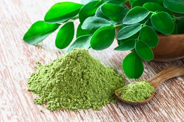 Moringa in polvere (moringa oleifera) con foglie di moringa fresche originali su fondo rustico.