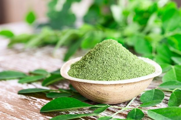 Moringa in polvere (moringa oleifera) in ciotola di cocco con originali foglie di moringa fresche