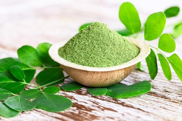 Moringa in polvere (moringa oleifera) in una ciotola di cocco con originali foglie fresche di moringa