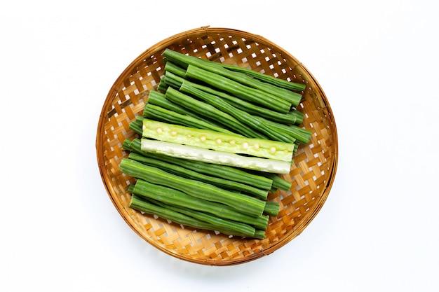 Moringa oleifera nel canestro di trebbiatura di bambù di legno su bianco