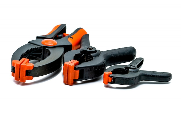 Morsetto a molla nero ed arancio isolato su fondo bianco. set di morsetti di plastica di piccole, medie e grandi dimensioni. strumenti di serraggio per lavori di carpenteria. utensili a mano per artigianato. attrezzatura di serraggio.