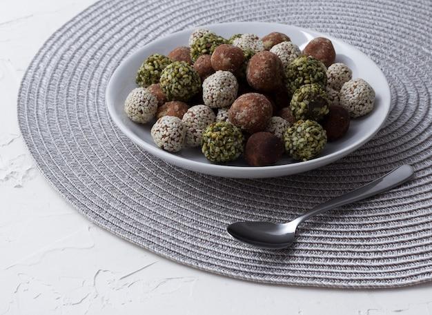 Morsi di energia biologica con datteri, semi di zucca, mandorle, noci e sesamo al tavolo bianco.