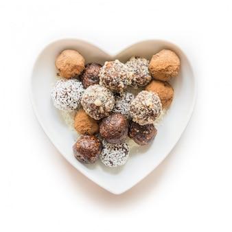 Morsi energetici fatti in casa, tartufi di cioccolato vegani con scaglie di cacao e cocco nel piatto come cuore. concetto di cibo sano.