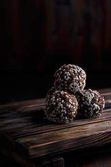 Morsi vegetariani organici di energia sana con noci, datteri, miele e sesamo su legno scuro
