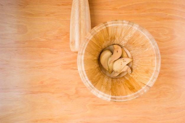 Mortaio con aglio secco in foto orizzontale su fondo di legno