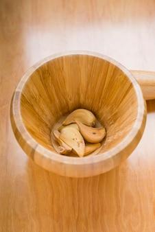 Mortaio con aglio secco in foto verticale su fondo di legno con luce posteriore