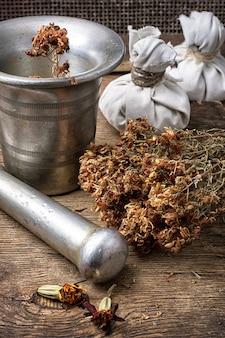 Mortaio di ferro e pestello con erbe medicinali essiccate in stile rurale.