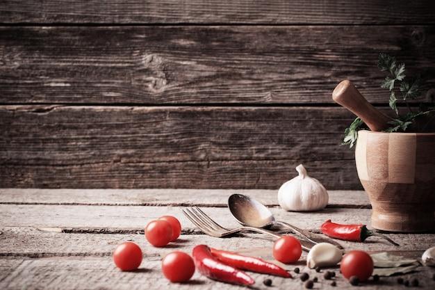 Mortaio e pestello con pepe e spezie sulla tavola di legno