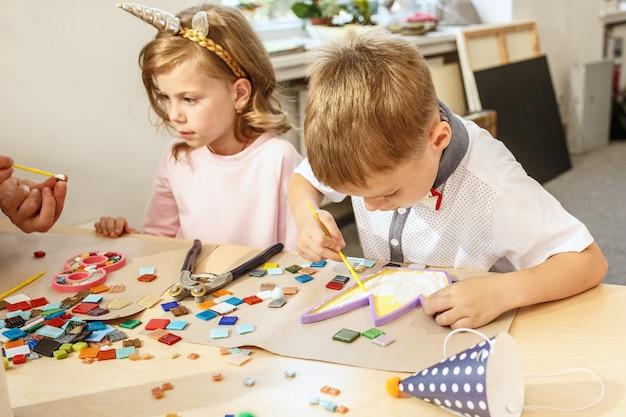 Mosaico puzzle art per bambini, gioco creativo per bambini. due sorelle giocano a mosaico